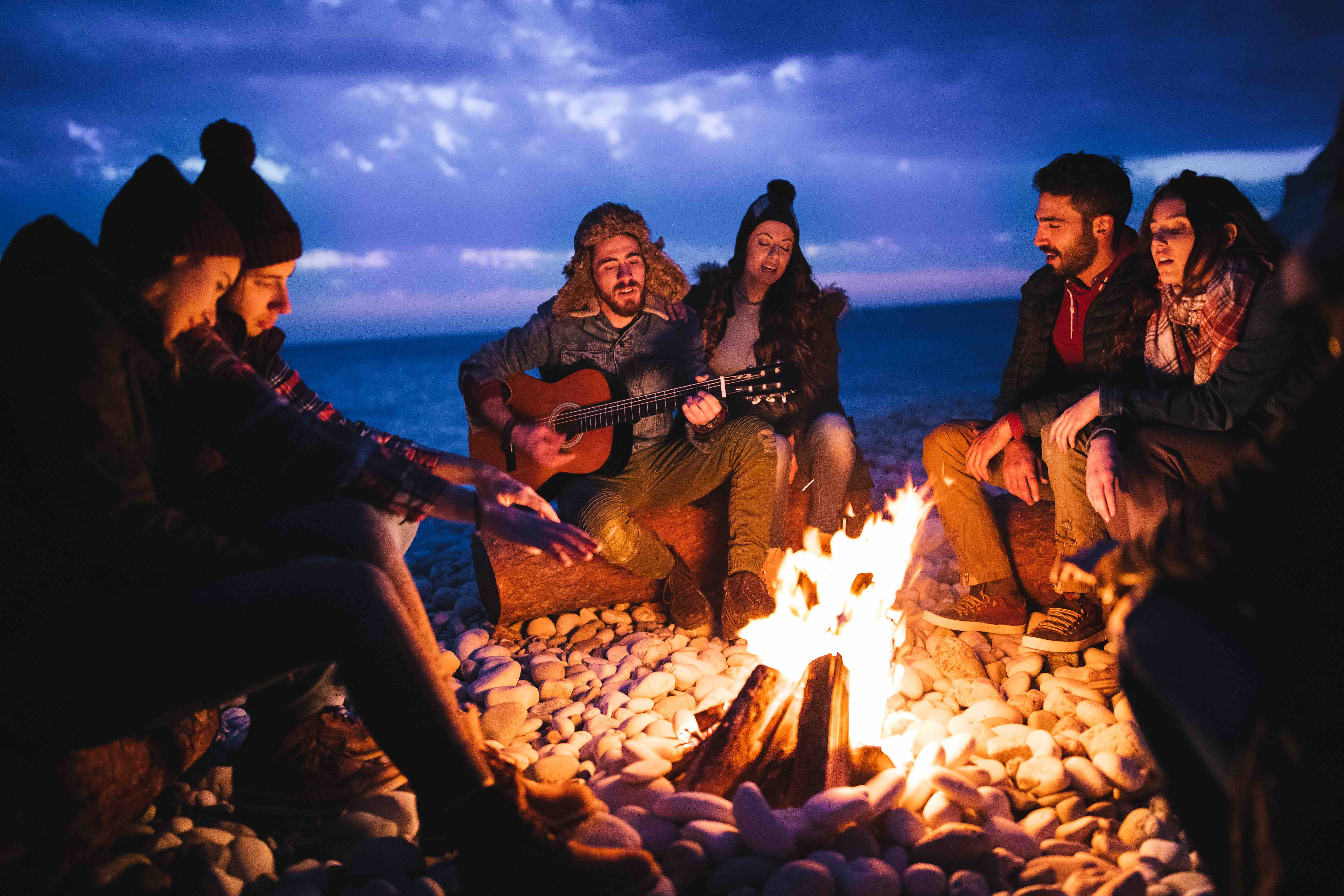 Friends playing guitar and singing around bonfire at the